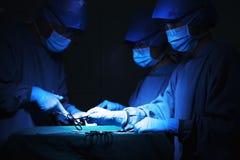 拿着外科设备的外科医生队在手术台和工作上 库存照片