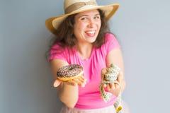 拿着多福饼和一卷测量的磁带的滑稽的少妇 甜点、不健康的速食和肥胖病的概念 免版税图库摄影