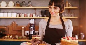 拿着多福饼和蛋糕在café的女服务员画象 影视素材