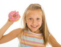拿着多福饼的年轻美好的愉快和激动的白肤金发的女孩8或9岁在看起来她的手上离开痉挛和快乐在sug 免版税库存图片