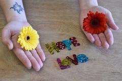 拿着多色的花的套手 免版税库存照片