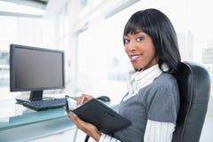 拿着大事记的微笑的女实业家 免版税库存图片