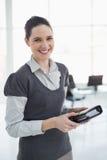拿着大事记的微笑的年轻女实业家 免版税图库摄影
