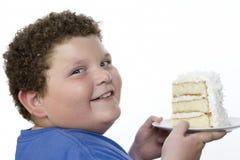 拿着大切片蛋糕的一个超重男孩的特写镜头 免版税库存图片