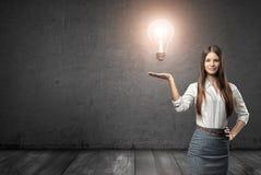 拿着大发光的电灯泡的一名年轻女实业家的播种的画象 免版税图库摄影