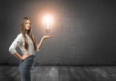拿着大发光的电灯泡的一名年轻女实业家的播种的画象 免版税库存图片