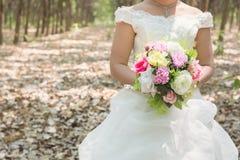 拿着大婚礼花束的新娘在森林里 库存图片