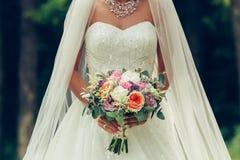 拿着大婚礼花束的新娘 免版税库存照片