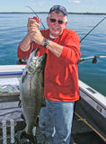 拿着大安大略湖大马哈鱼鱼的人 库存照片