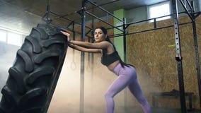 拿着大拖拉机轮胎和看对照相机的坚强的年轻女人在健身房的交叉训练锻炼期间 股票录像