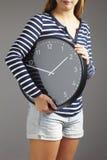 拿着大时钟的妇女 免版税库存图片