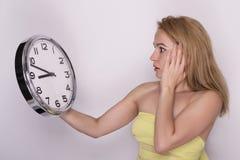 拿着大时钟的年轻美丽的妇女 背景概念查出的目的程序时间白色 库存图片