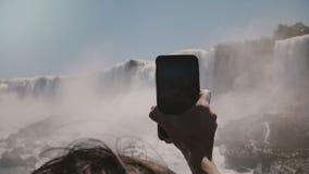 拿着大智能手机的慢动作特写镜头人的手为难以置信的尼亚加拉大瀑布瀑布全景照相 股票录像