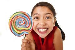 拿着大桃红色螺旋棒棒糖糖果的甜美丽的拉丁女孩 免版税库存图片