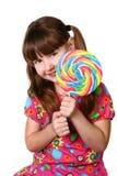 拿着大棒棒糖的逗人喜爱的女孩 库存照片