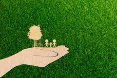 拿着大植物树家庭的生态概念人的手 库存照片