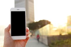 拿着大模型智能手机有都市风景背景的手 图库摄影