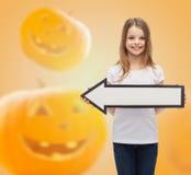 拿着大白色箭头的微笑的小女孩 免版税图库摄影
