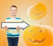 拿着大白色箭头的微笑的小男孩 库存照片