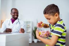拿着大碗用糖果的逗人喜爱的滑稽的男孩选择一 免版税库存图片