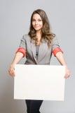 有空白的白色标志的典雅的年轻女实业家。 免版税库存图片
