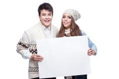 拿着大符号的新微笑的冬天夫妇 库存图片
