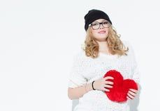 拿着大红色心脏和摆在白色墙壁附近的白色毛线衣的美丽的时兴的快乐的女孩 在工作室 图库摄影