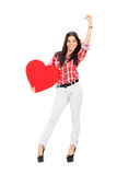 拿着大红色心脏的可爱的妇女 免版税库存图片