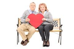 拿着大红色心脏的可爱的成熟夫妇 免版税库存图片