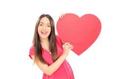 拿着大红色心脏的女孩 免版税库存图片