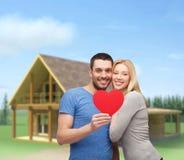 拿着大红色心脏的微笑的夫妇 免版税库存图片