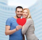 拿着大红色心脏的微笑的夫妇 库存照片