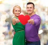 拿着大红色心脏的微笑的夫妇 库存图片