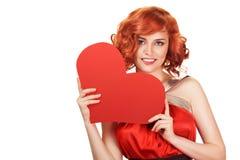 拿着大红色心脏的微笑的红色头发妇女画象  库存照片