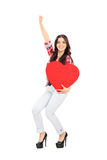 拿着大红色心脏的极度高兴的妇女 库存照片