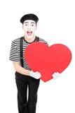 拿着大红色心脏的男性笑剧艺术家 库存图片