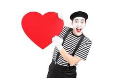 拿着大红色心脏的笑剧艺术家 免版税库存图片