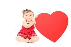 拿着大红色心脏的逗人喜爱的矮小的婴孩 免版税库存照片