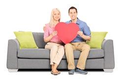 拿着大红色心脏的年轻夫妇供以座位在沙发 库存图片