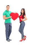 拿着大红色心脏的年轻夫妇 免版税图库摄影
