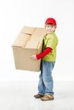 拿着大纸盒配件箱的男孩。 库存照片