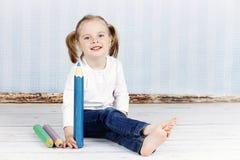 拿着大蜡笔的聪明的小女孩 免版税库存照片