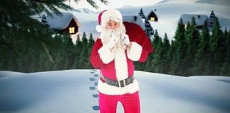 拿着大袋和保留秘密的圣诞老人的综合图象 免版税库存照片