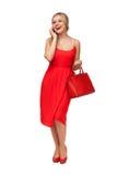 拿着大袋子的红色礼服的妇女谈话在手机 免版税库存照片