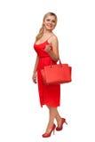 拿着大袋子的红色礼服的白肤金发的美丽的妇女 免版税库存图片