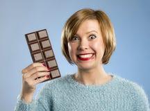 拿着大酒吧嘴的愉快的巧克力上瘾者妇女被弄脏的和疯狂的激动的面孔表示 免版税库存图片
