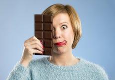 拿着大酒吧嘴的愉快的巧克力上瘾者妇女被弄脏的和疯狂的激动的面孔表示 免版税图库摄影