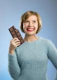 拿着大酒吧嘴的愉快的巧克力上瘾者妇女被弄脏的和疯狂的激动的面孔表示 图库摄影