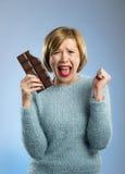 拿着大酒吧嘴的愉快的巧克力上瘾者妇女被弄脏的和疯狂的激动的面孔表示 免版税库存照片