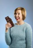 拿着大酒吧嘴的愉快的巧克力上瘾者妇女被弄脏的和疯狂的激动的面孔表示 库存照片
